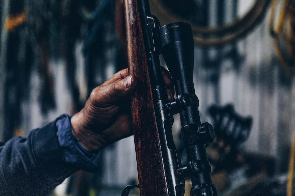 A man's hand holding a hunting rifle