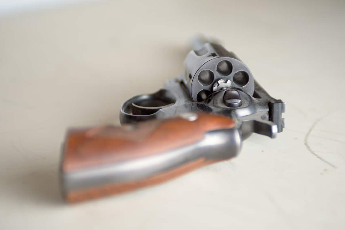Closeup view of unarmed metal revolver gun placed on white desk