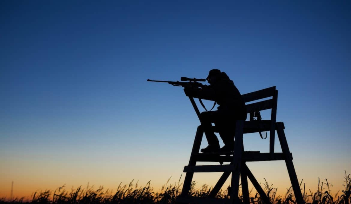 Hunter sitting in lookout tower by dusk shooting .30-06 rifle