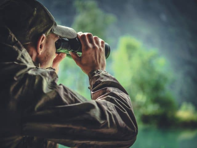 Caucasian Hunter in Masking Camouflage Uniform with Binoculars. Hunter Spotting Game. Poacher or Soldier Clothing. (Caucasian Hunter in Masking Camouflage Uniform with Binoculars. Hunter Spotting Game. Poacher or Soldier Clothing., ASCII, 115 componen