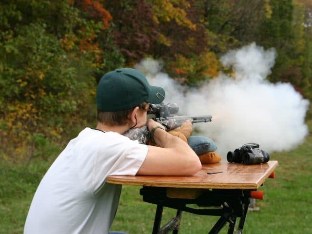 A Muzzle Loader Rifle emits smoke and fire as it is fired from a shooting bench wiht fall colors in the background.