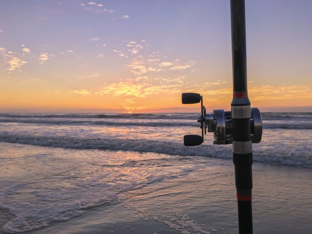 Fishing rod on beach at sunset, surfing cast.