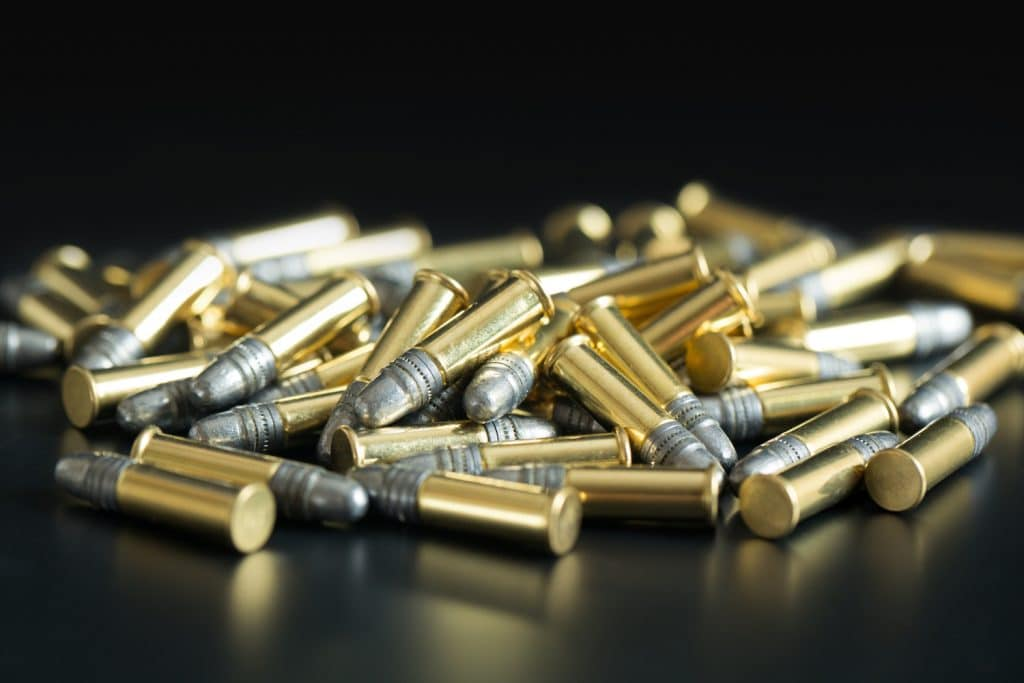 Photo of .22 caliber bullets in a pile on a black background.