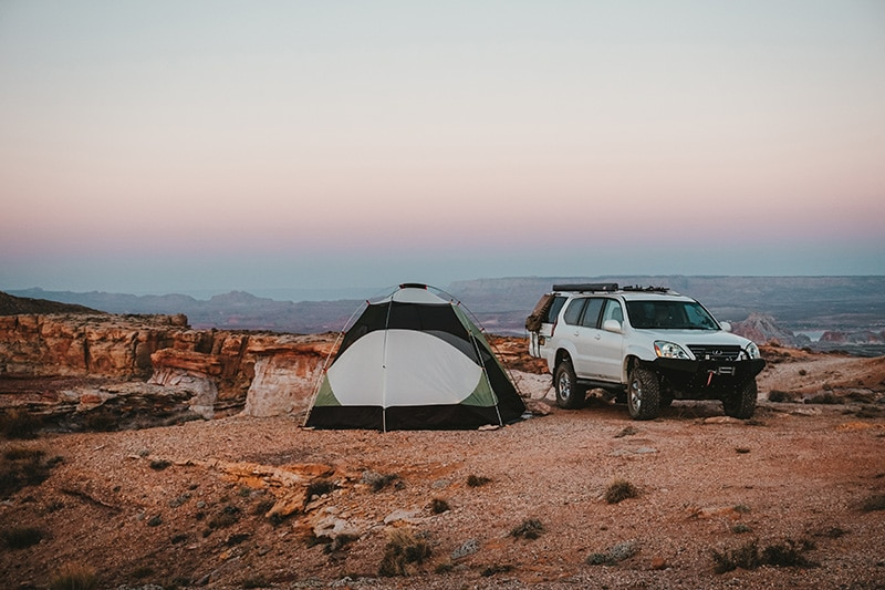 Tent and SUV set up at a free campsite on a red mountain