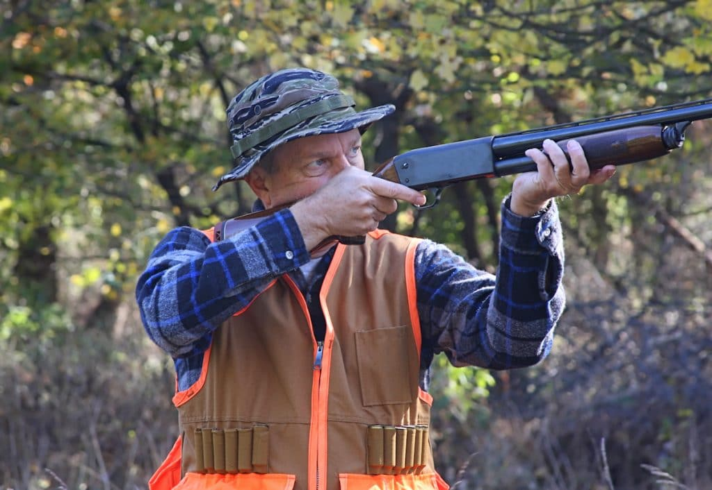 man shooting a 12-gauge while hunting