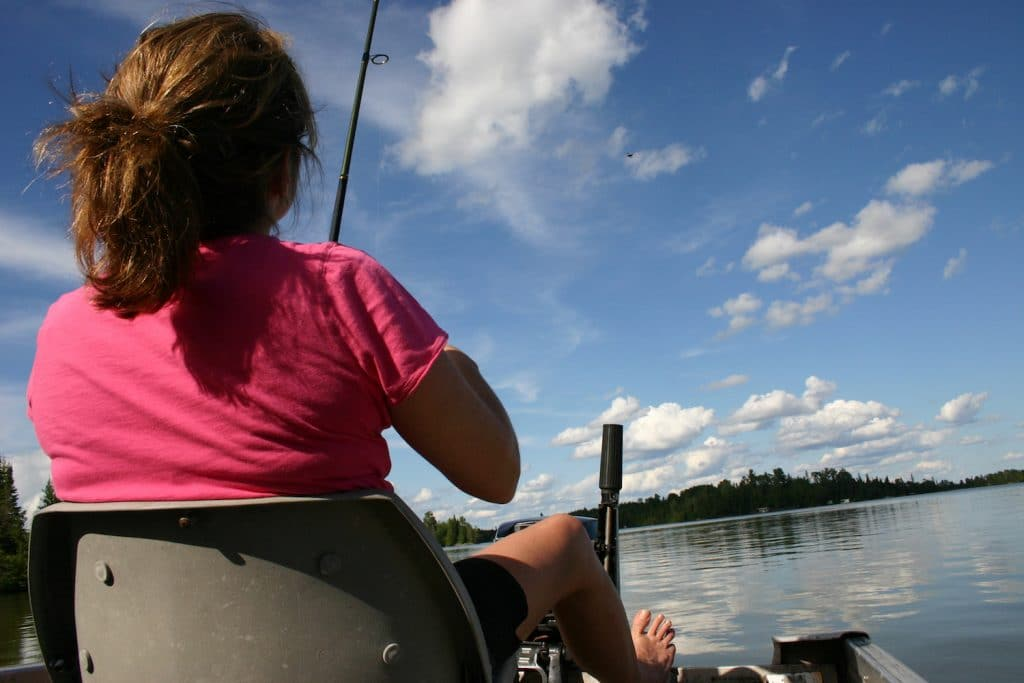 Girl fishing from boat in Ontario lake.