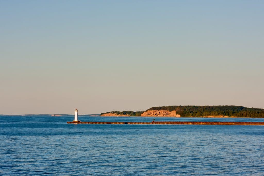 Sodus Bay Lighthouse on Lake Ontario in evening sunlight just before sunset