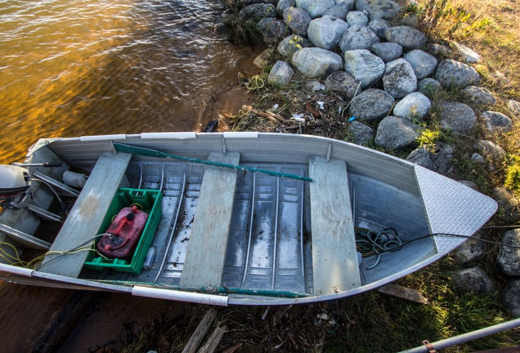 Aluminum rowboat in the water and anchored on the shores of Lake Superior. The small fishing boat is equipped with a small boat motor.