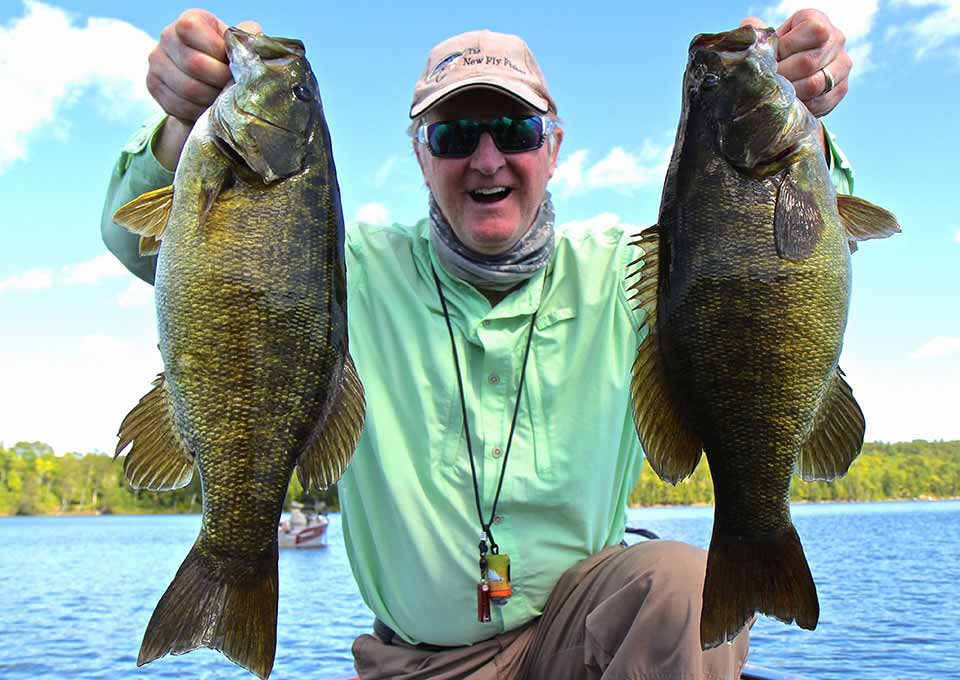 Man holding two smallmouth bass near a lake