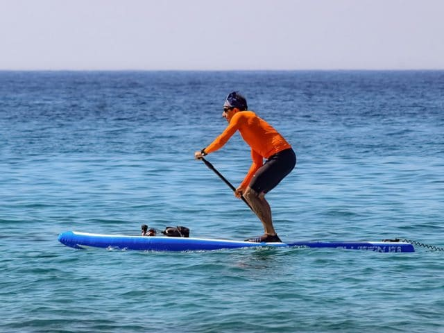Man racing a paddleboard in the ocean
