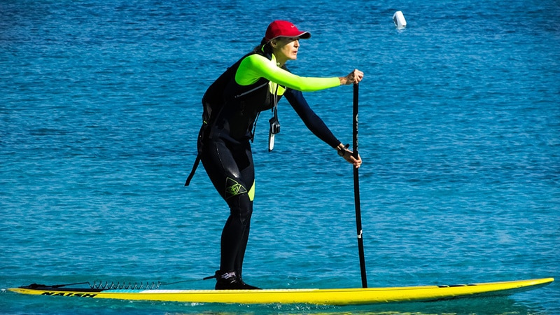 Woman racing a paddleboard with all her gear