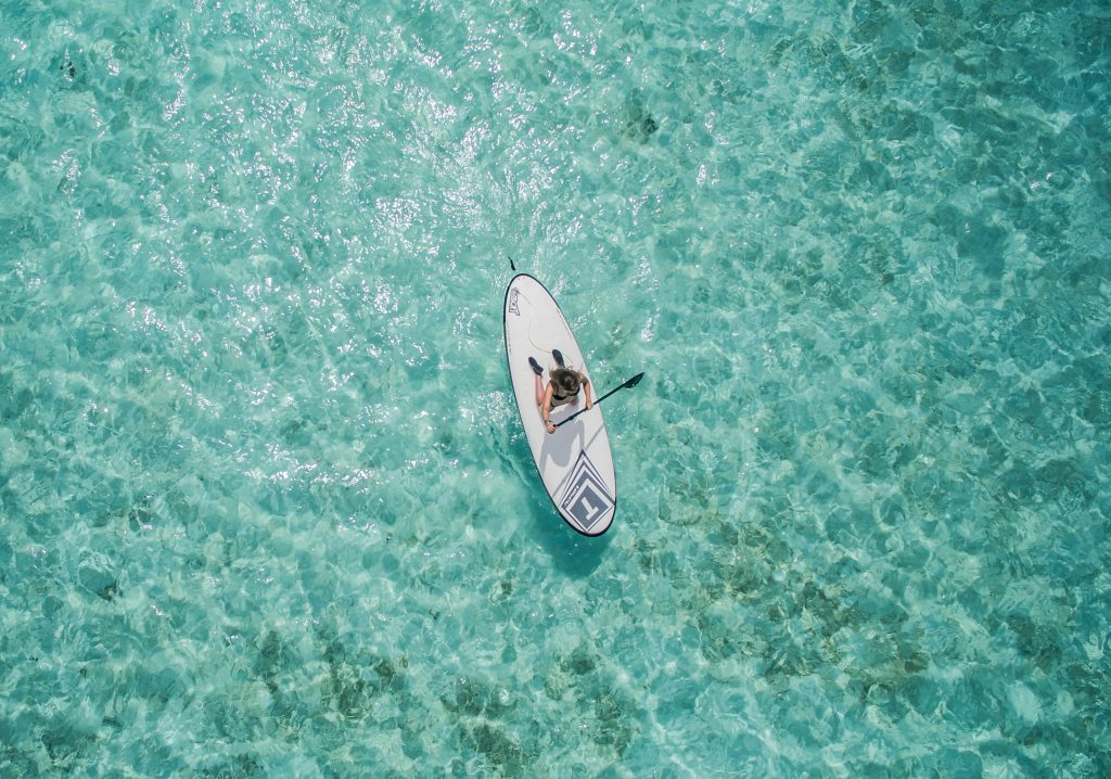 Man on a paddleboard in clear blue water
