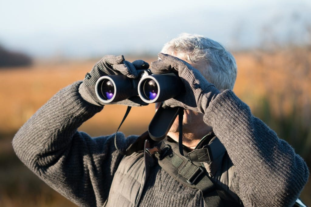 Gray haired man with binocular
