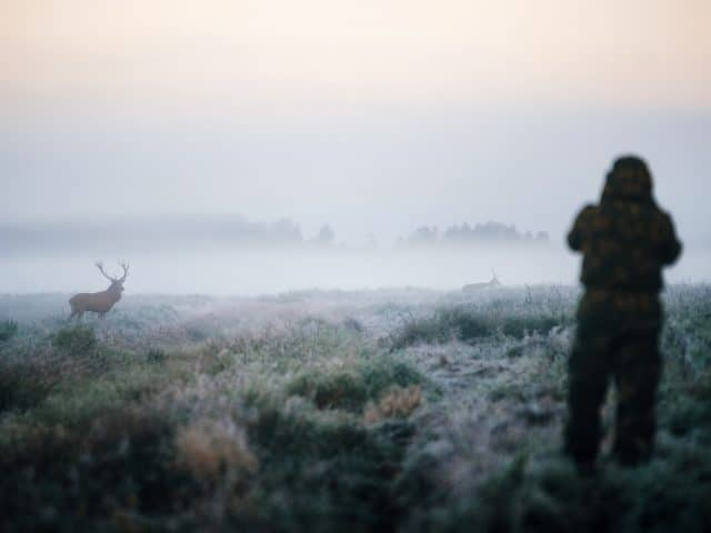 Hunter holding a rifle and aiming red deer prey in the mist, hunter photoshooting at the morning.