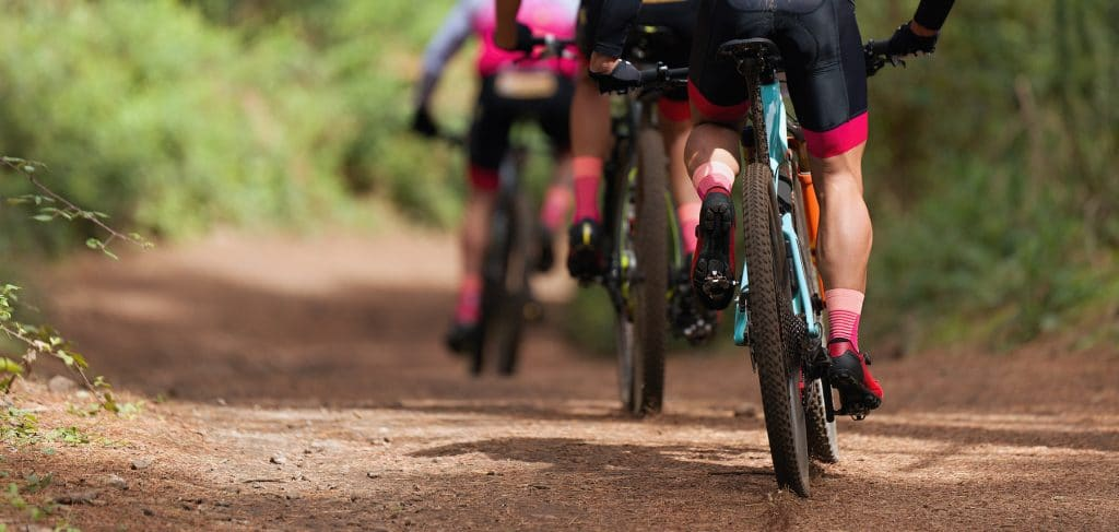 Group of athletes mountain biking on forest trail, mountain bike race