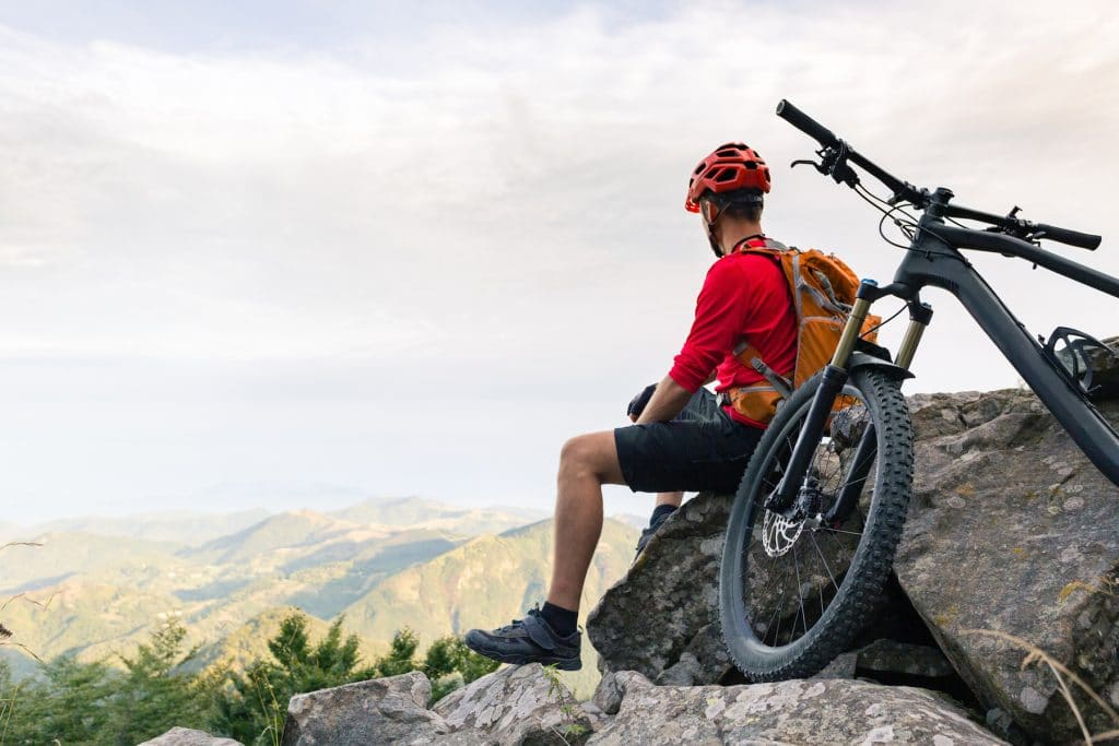 Mountain biker looking at inspiring landscape on bike rocky trail in autumn mountains. Riding on full suspension bike. Sport fitness, motivation and inspiration in beautiful inspirational landscape. (Mountain biker looking at inspiring landscape on bi