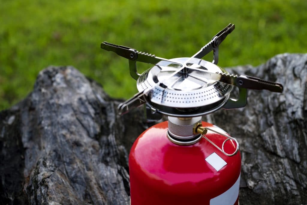 Red Portable gas Camping stove on a rock (Backpack Concept)