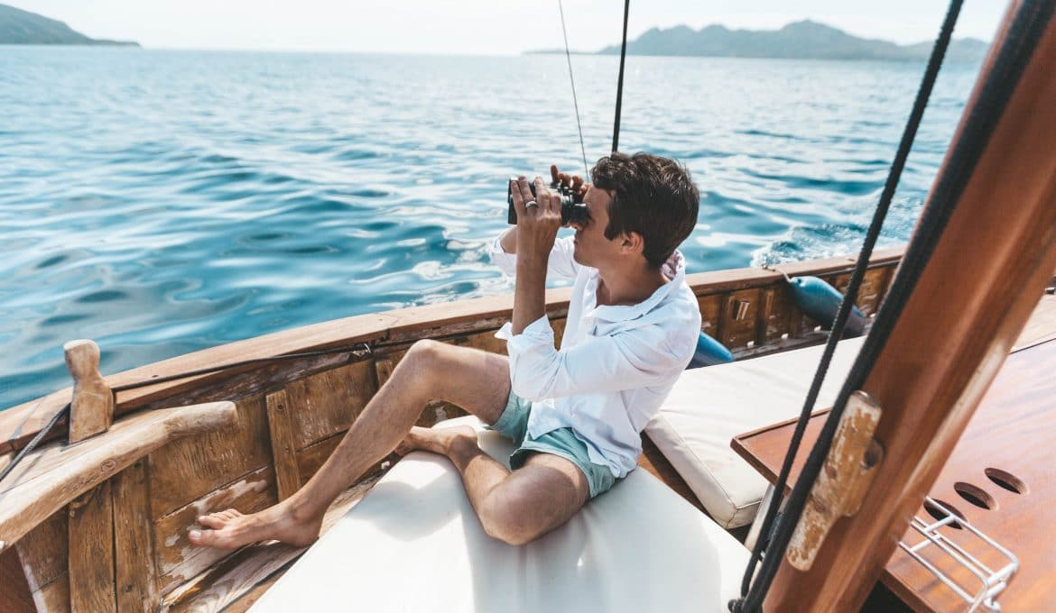 Man using binoculars on a sailboat
