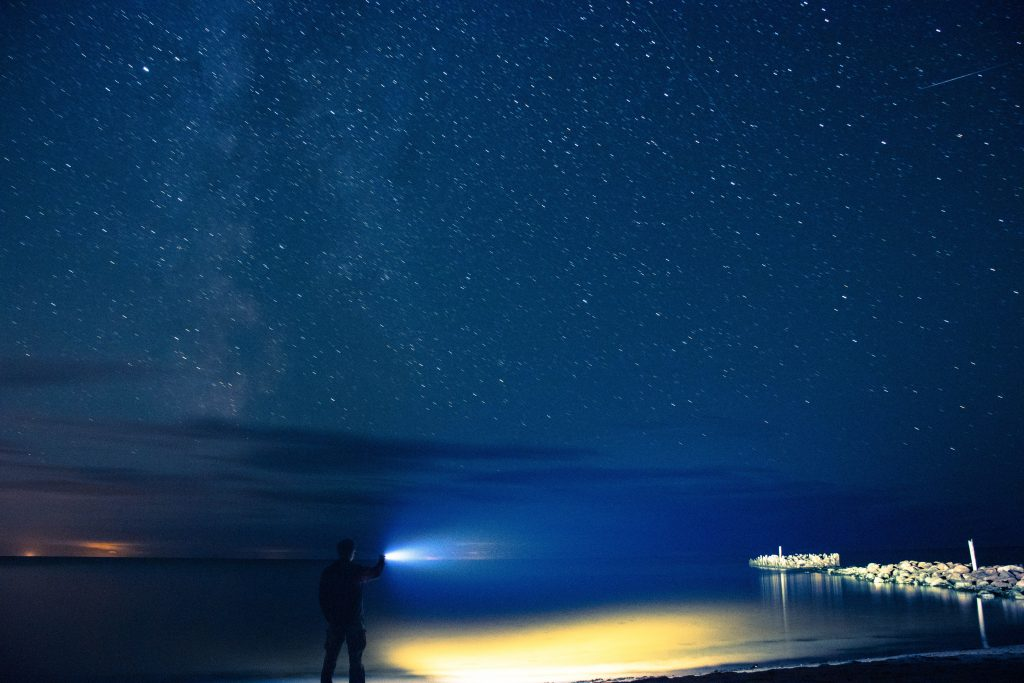 Man standing on shore holding a flashlight during a starry night