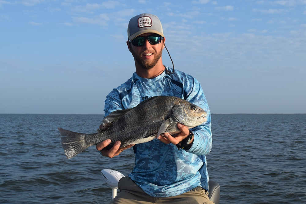 Man holding a black drum fish