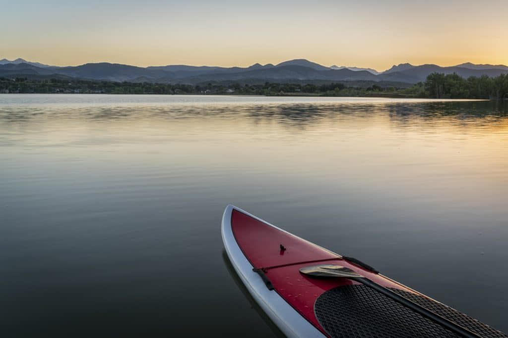 stand up paddleboard with a paddle on calm lake at dusk with Rocky Mountains in background
