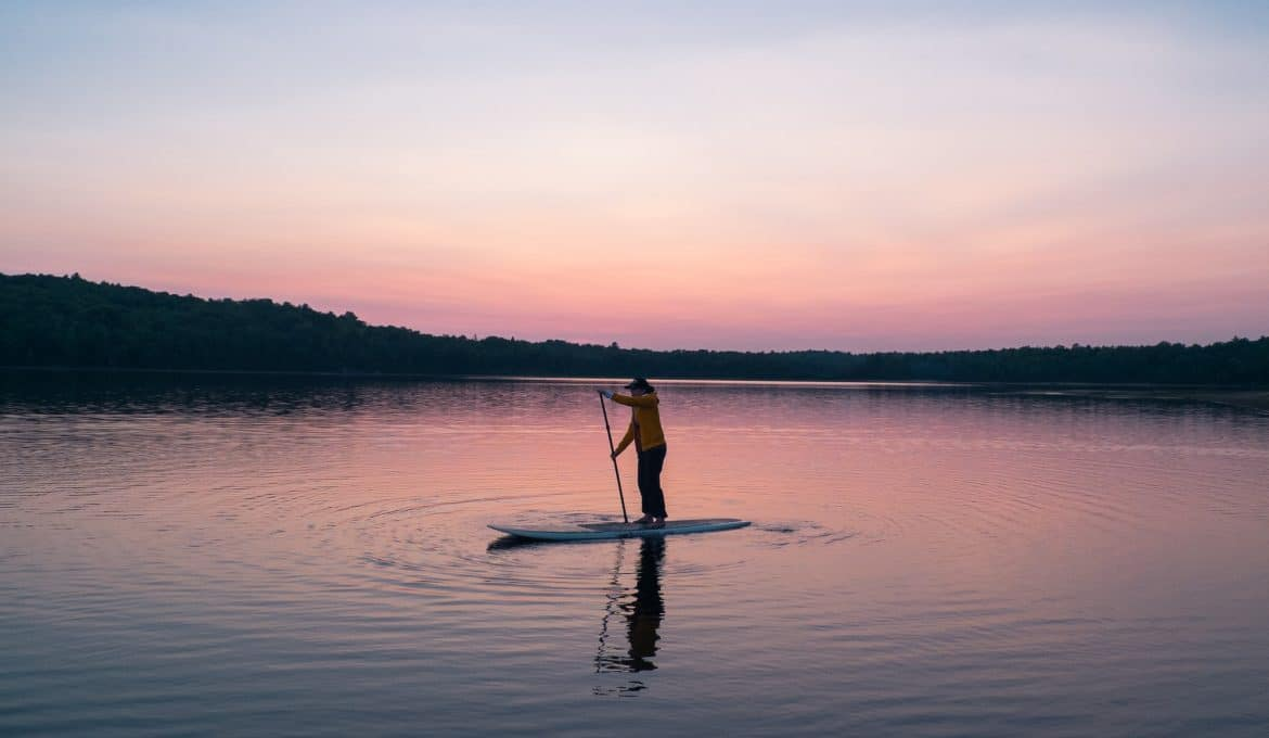 Paddleboarder on a lake at sunset
