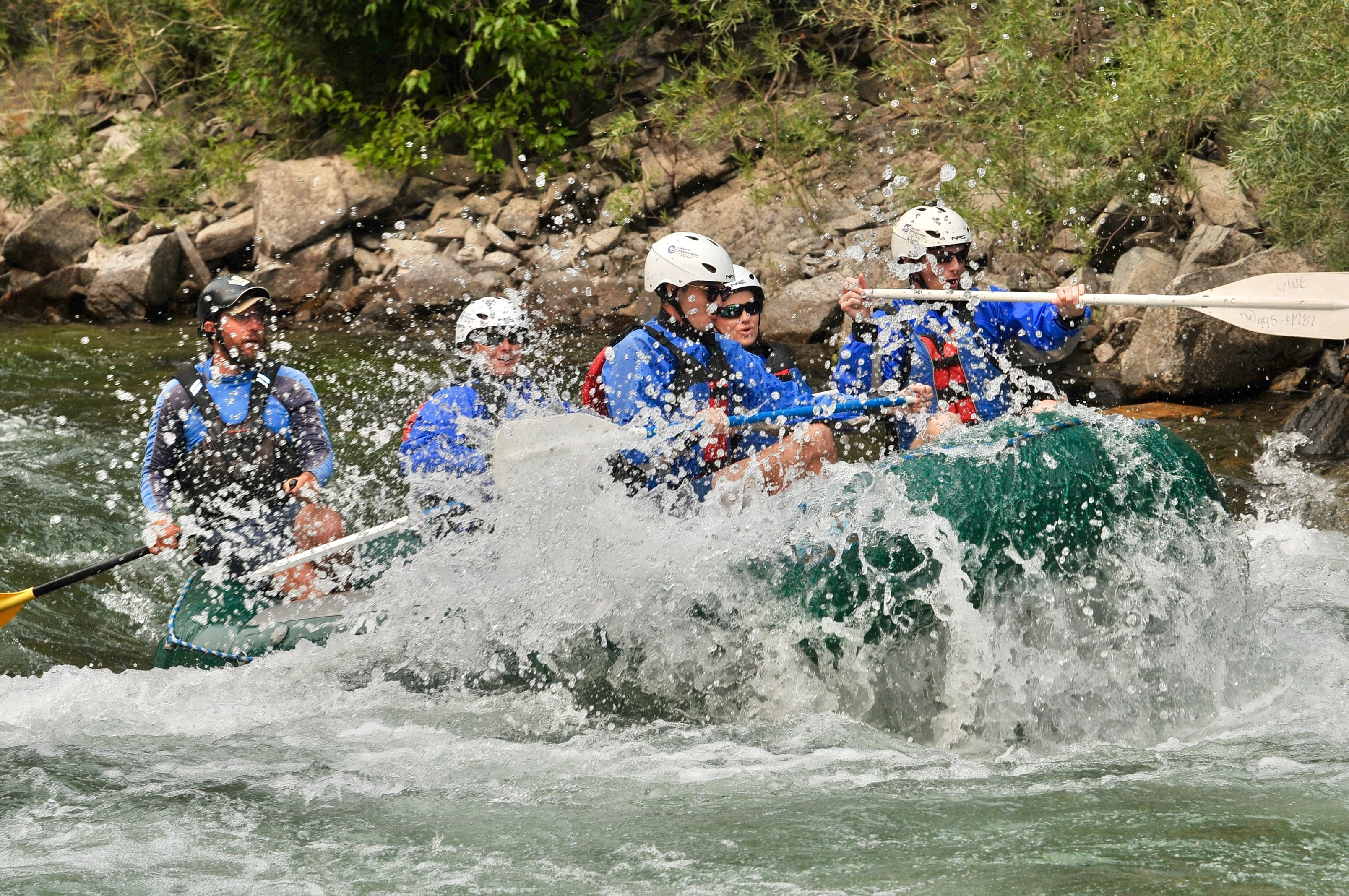 Rafters getting splashed on a rafting trip.