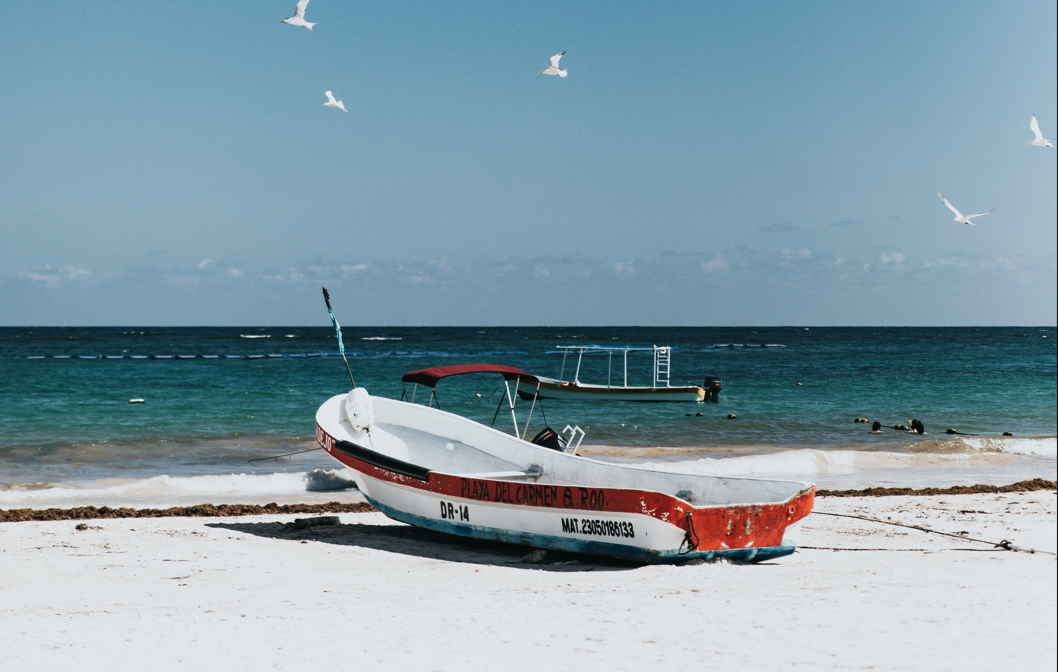 Fishing boat stored on sandy beach.