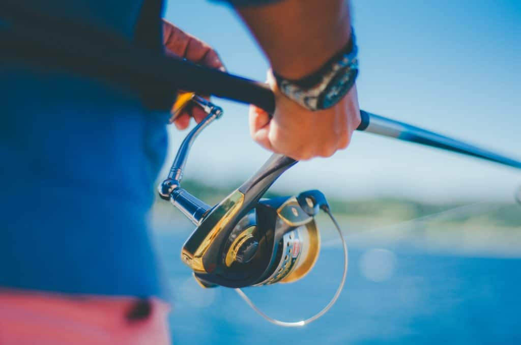 Man holding spinning reel in hand while jigging for bass