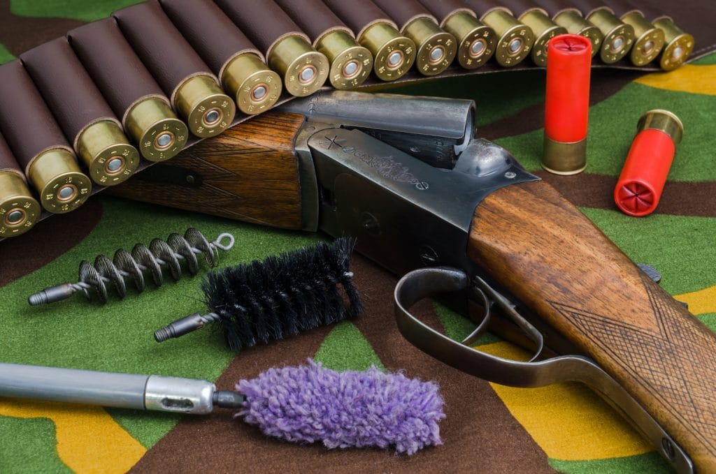 Hunting rifle and ammunition with brushes for cleaning weapons lying on a camouflage backround.