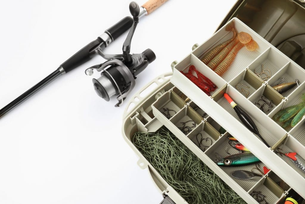 Box with tackle and fishing rod on white background