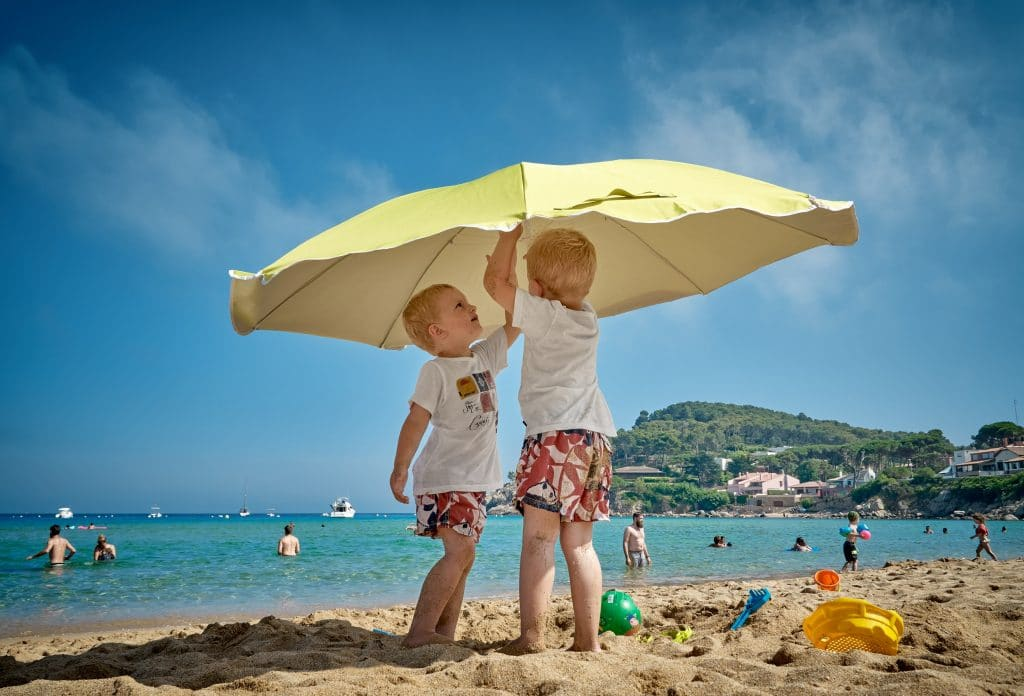 kids playing under a beach umbrella