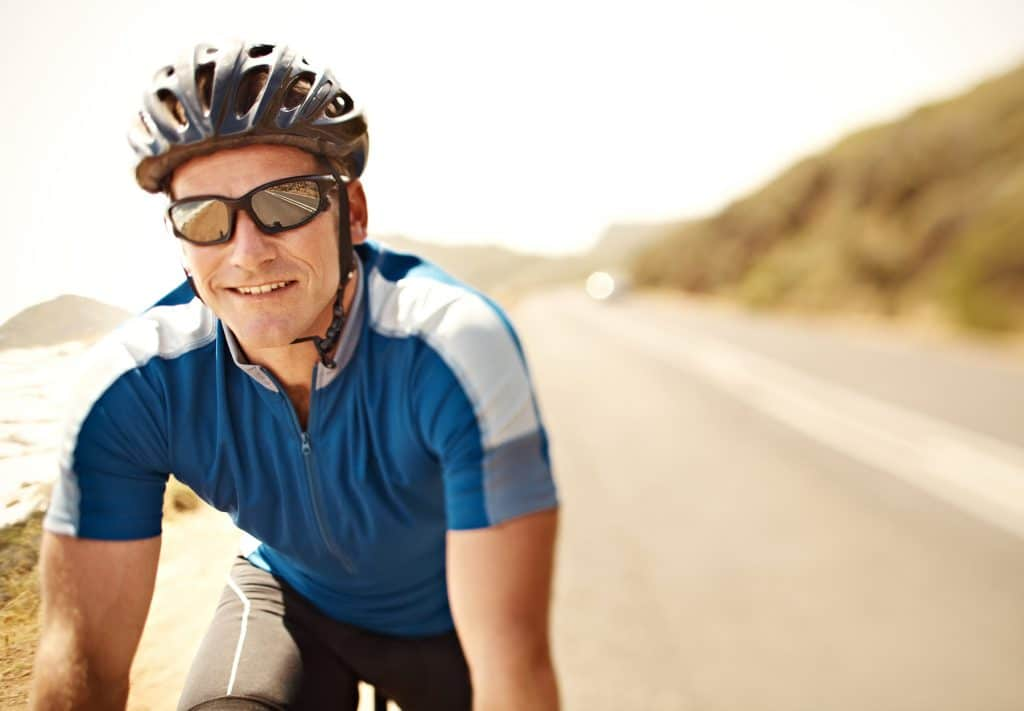 Smiling mature man on a bicycle with copyspace behind him