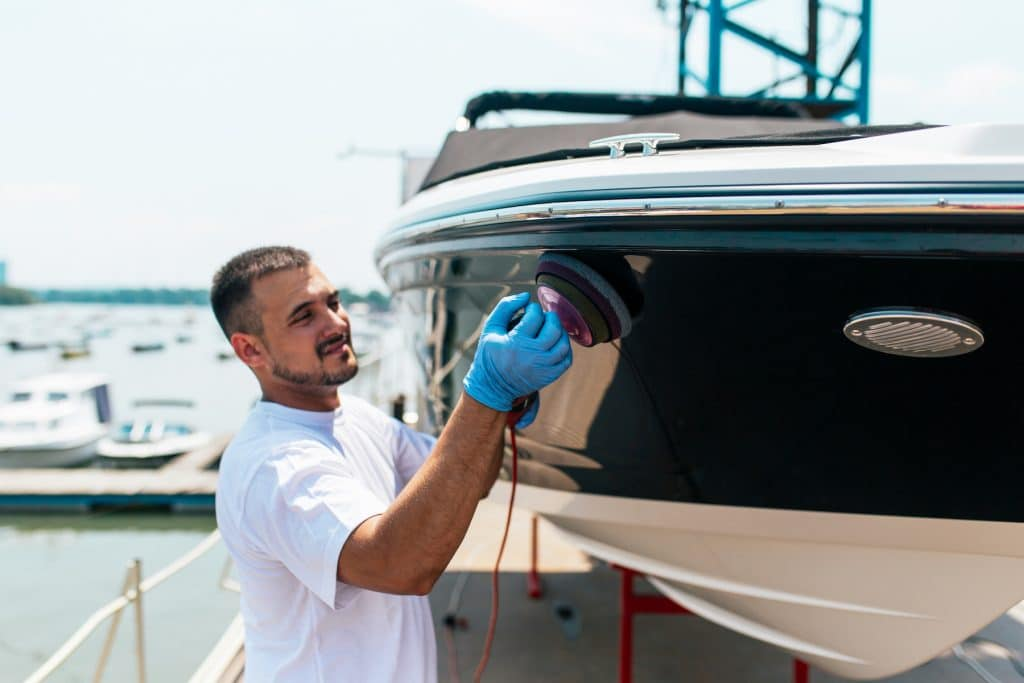 Boat maintenance - Man with orbital polisher polishing boat in marina.