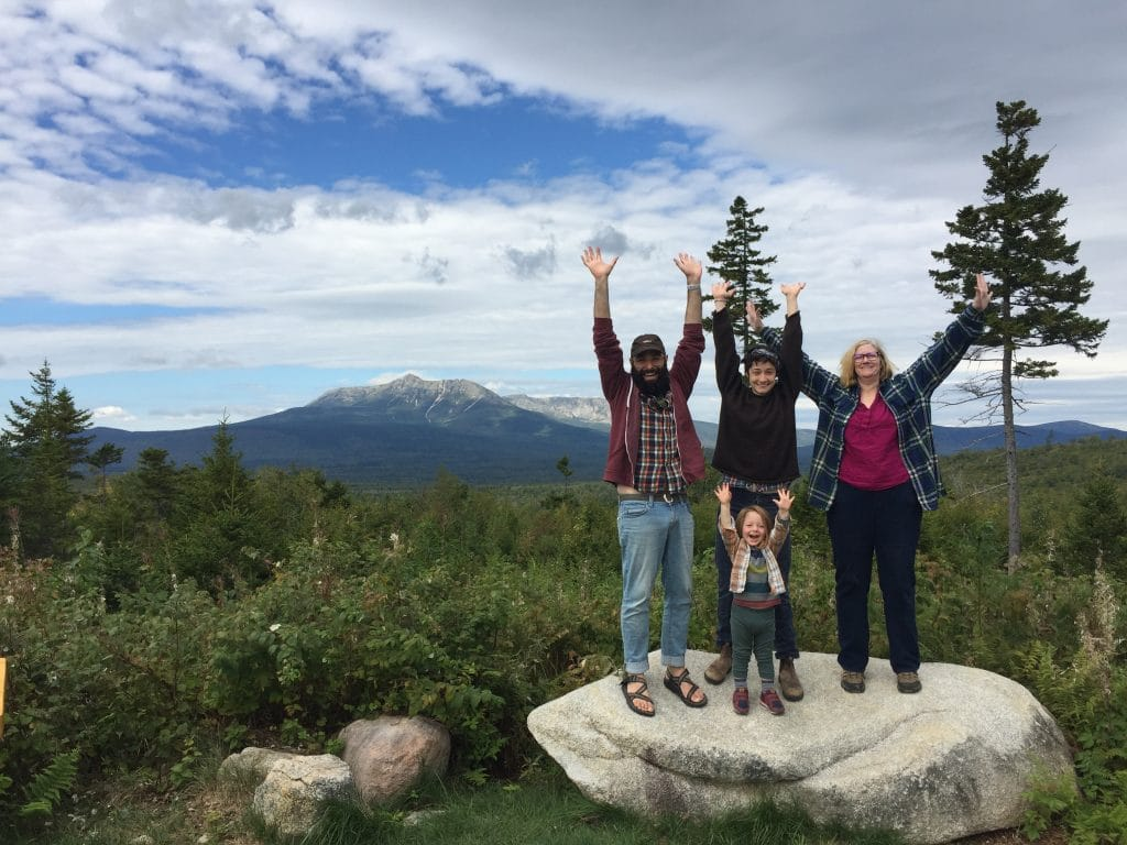 Three adults and one young child raise both arms above their heads