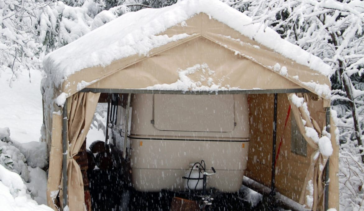 A holiday travel trailer is seen parked in a outdoor garage. It is snowy day and the trailer appears to be thinking when is summer coming?