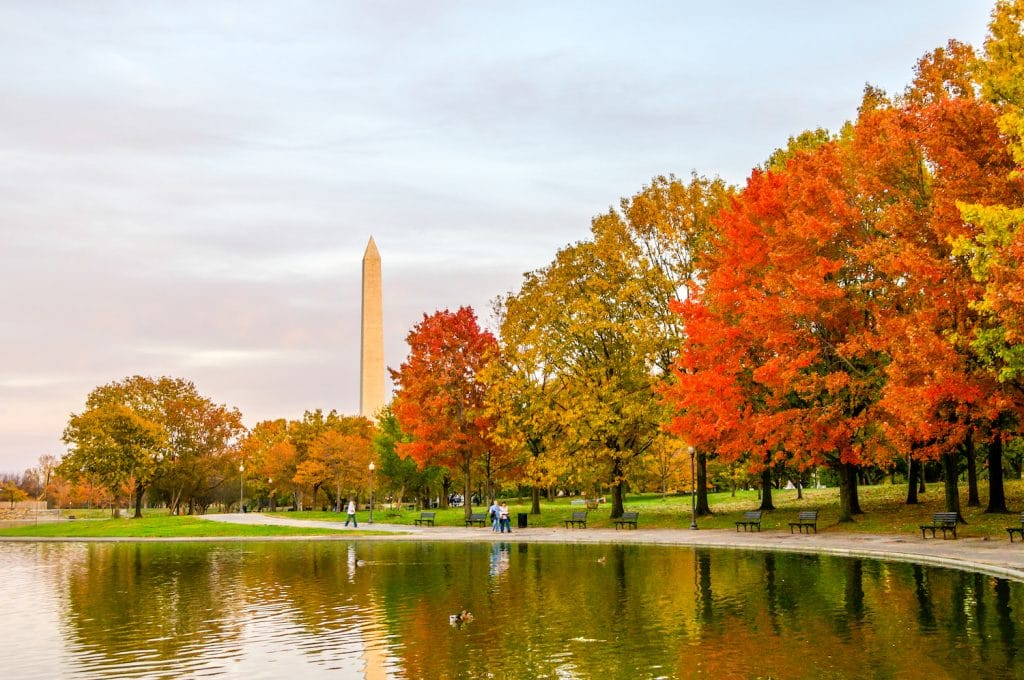 Fall colors brighten the shoreline of a pond reflecting them and the Washington Monument in Washington D.C.
