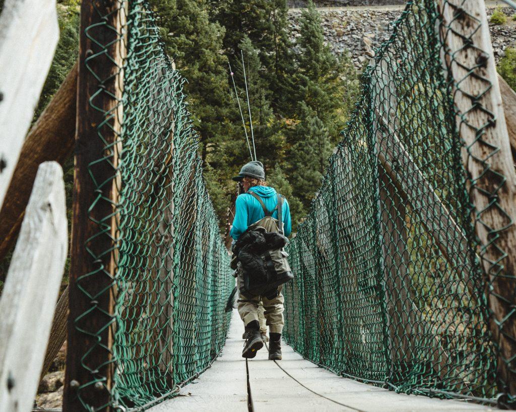Man walking on bridge with fishing poles