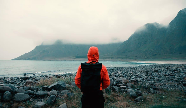 Man in Orange Jacket on Rainy Coastline