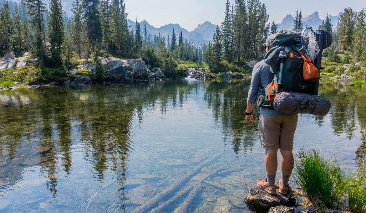 Man backpacking by mountain stream