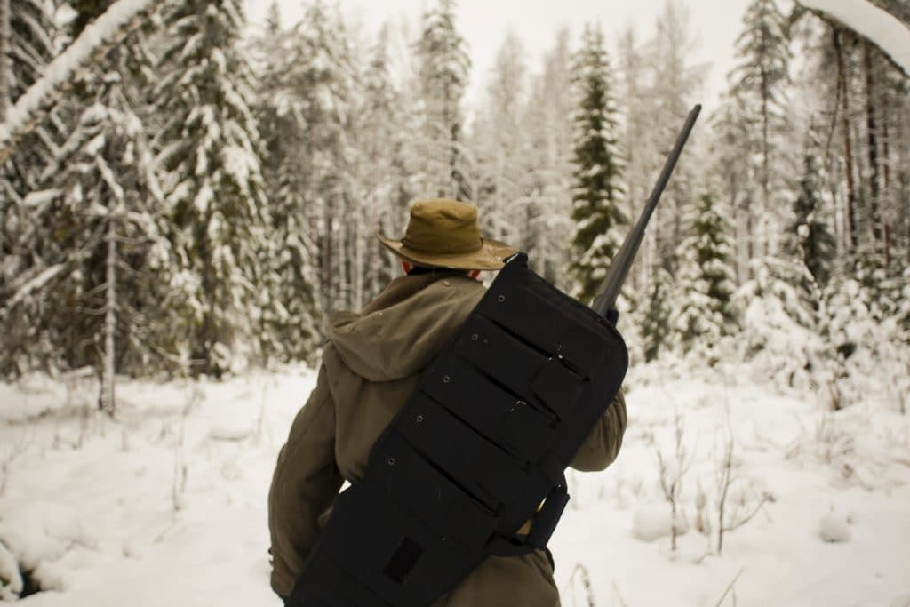 Man with gun in hands is hunting in the winter forest. He is turned back to the camera.