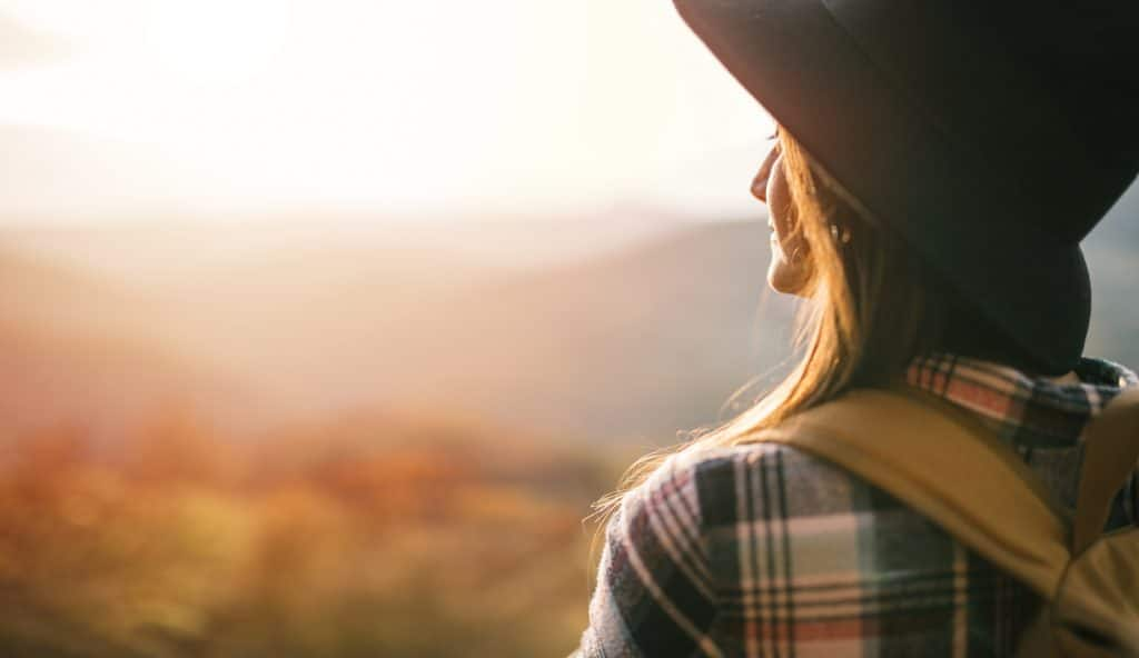 Side view of young travel woman with hat and backpack enjoy sunset.
