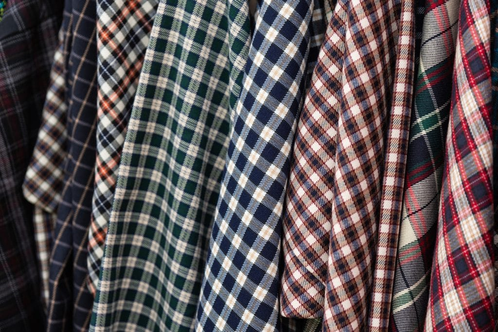 Details of a check or lumberjack flannel shirts which hang in a row