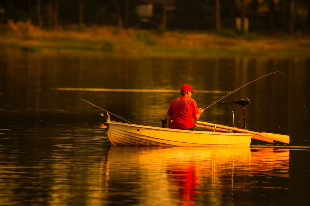 Man in red cap and shirt fishing from silver boat