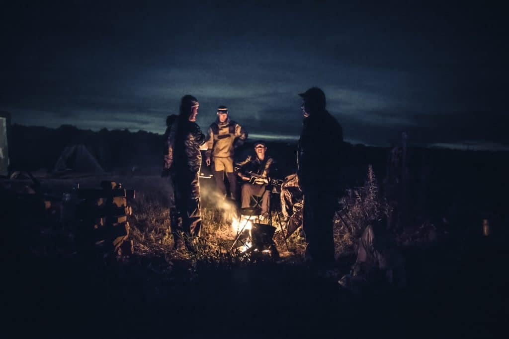 group of hunters standing around a fire