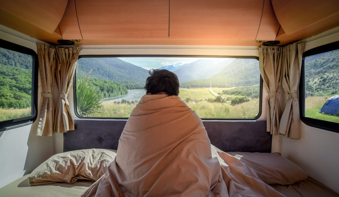 Young Asian man staying in the blanket looking at mountain scenery through the window in camper van in the morning. Road trip in summer of South Island, New Zealand. (Young Asian man staying in the blanket looking at mountain scenery through the windo