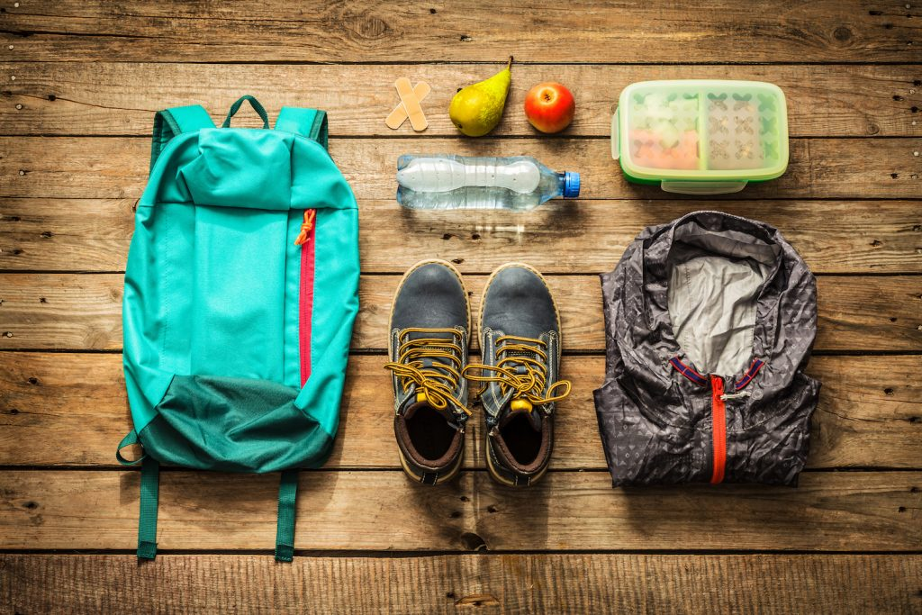 Traveling - packing (preparing) for adventure school trip concept. Backpack, boots, jacket, lunch box, water and fruits on wooden background captured from above (flat lay). (Traveling - packing (preparing) for adventure school trip concept. Backpack,