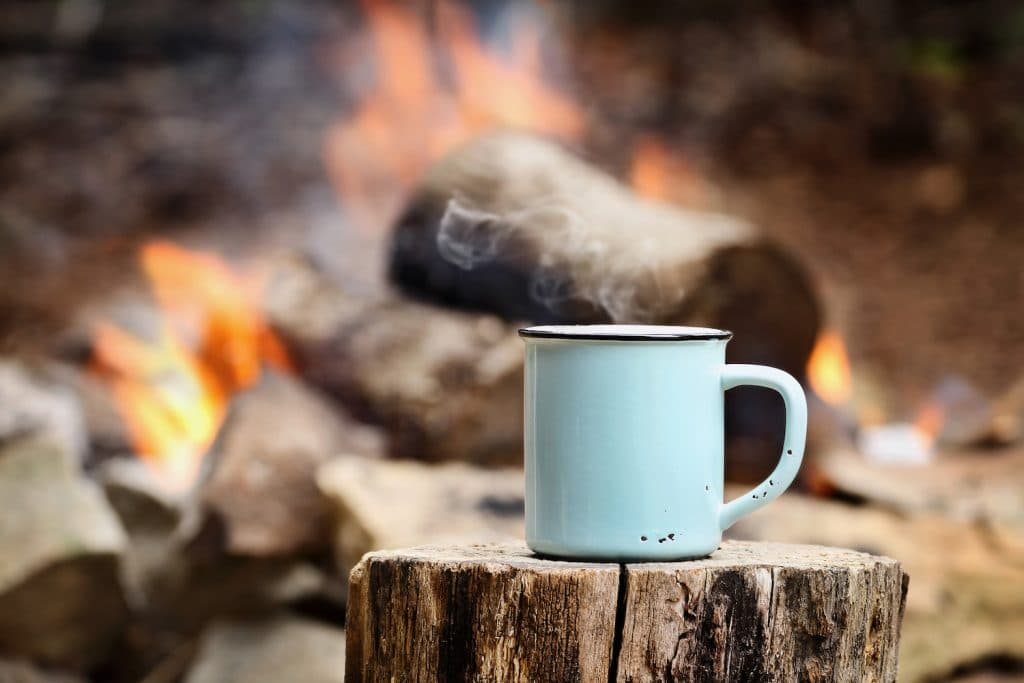 Blue enamel cup of hot steaming coffee sitting on an old log by an outdoor campfire. Extreme shallow depth of field with selective focus on mug. (Blue enamel cup of hot steaming coffee sitting on an old log by an outdoor campfire. Extreme shallow dept