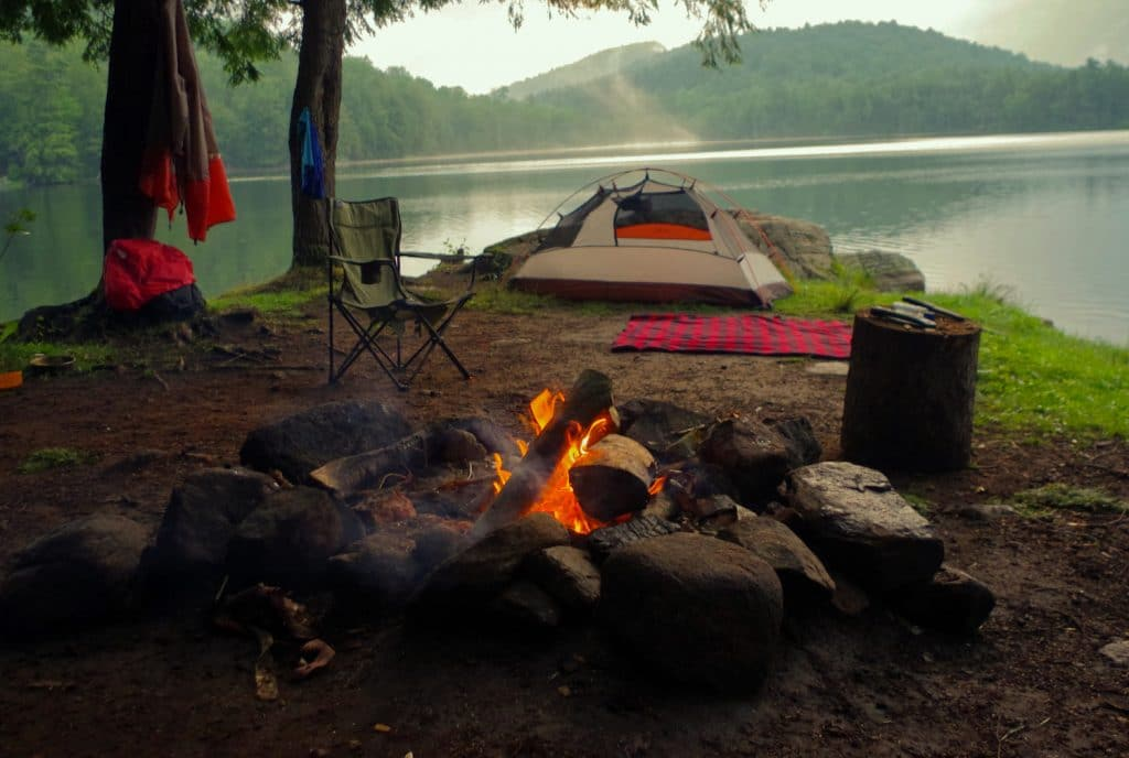 Campfire outside of tent and campsite on a lake in the Adirondack Mountains.