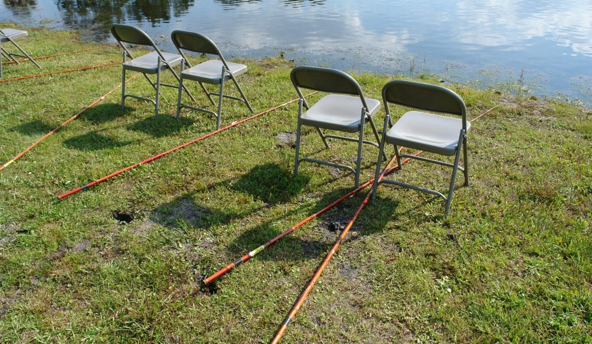 Five empty blue fold-up chairs and six cane poles sit arranged side by side in front of a pond. There is short green grass on the ground.